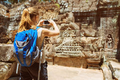 Tourist taking photo of bas-reliefs in temple. Angkor, Cambodia Stock Photo