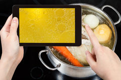 Tourist taking photo of boiling of chicken broth Royalty Free Stock Image
