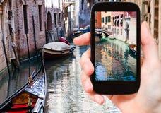 Tourist taking photo of canal, gondola, boats Stock Photography