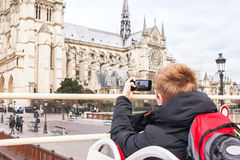 Tourist taking photo on cathedral of Notre Dame de Paris. Stock Photo