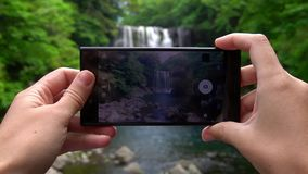 Tourist taking photo of Cheonjeyeon waterfall on Jeju Island, South Korea with Mobile Phone. Active Tourism in Asia stock video