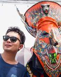 Tourist taking photo with colorful mask performer in Phi Ta Kon Royalty Free Stock Photo