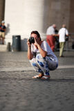 Tourist taking a photo crouching Royalty Free Stock Photography