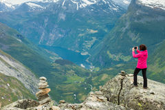 Tourist taking photo from Dalsnibba viewpoint Norway. Tourism vacation and travel. Female tourist taking photo with camera, enjoying Geiranger fjord and Stock Images