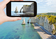Tourist taking photo of english channel with cliff. Travel concept - tourist taking photo of english channel coast with cliffs on Etretat cote d'albatre, France Stock Photo