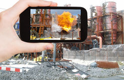 Tourist taking photo of explosion at factory Stock Photo
