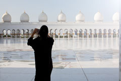 Tourist taking photo at famous Grand Mosque in Abu Dhabi. Woman using smart phone in UAE Royalty Free Stock Image
