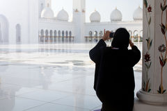 Tourist taking photo at famous Grand Mosque in Abu Dhabi. Woman using smart phone in UAE Stock Image
