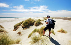Tourist taking photo of Farewell spit sand dunes. And ocean. New Zealand royalty free stock photo