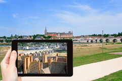 Tourist taking photo of Gien town, France. Travel concept - tourist taking photo of Gien town in valley of Loire River on mobile gadget, France Stock Photo