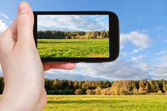 Tourist taking photo of green meadow in autumn Royalty Free Stock Photography