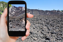 Tourist taking photo of lava flow on slope of Etna Stock Photography