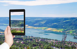 Tourist taking photo of Lillehammer town in Norway. Travel concept - tourist taking photo of Lillehammer town in Norway on mobile gadget Stock Photo