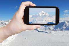 Tourist taking photo of mountain peak in Alpes Royalty Free Stock Photo