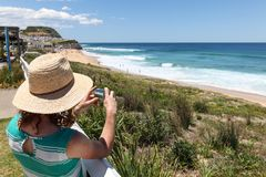 Tourist taking photo - Newcastle Australia. A woman tourist takes a photo of Bar Beach - Newcastle Australia on a beautiful day. Newcastle is Australia`s second royalty free stock photo