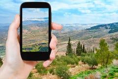 Tourist taking photo of Promised Land. Travel concept - tourist taking photo of Promised Land from Mount Nebo in Jordan on mobile gadget Stock Images