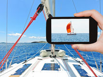 Tourist taking photo of red yacht in Adriatic sea Royalty Free Stock Photo