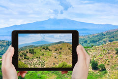 Tourist taking photo of rural landscape with Etna Stock Photos