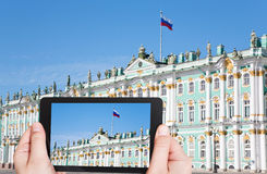 Tourist taking photo of Russian state flag. Travel concept - tourist taking photo of Russian state flag on Winter Palace, St.Petersburg, Russia on mobile gadget royalty free stock images