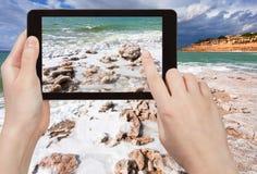Tourist taking photo of salt beach on Dead Sea Stock Photos