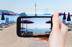 Tourist taking photo of sand beach Giardini Naxos Royalty Free Stock Photography