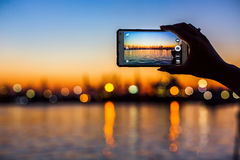Tourist taking photo of sea harbor with mobile device at sunset Stock Images