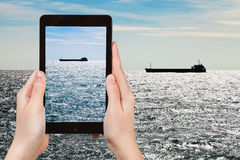 Tourist taking photo ship in Black sea in evening Royalty Free Stock Images