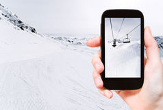 Tourist taking photo of skiing tracks and ski lift Royalty Free Stock Image