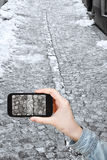 Tourist taking photo of snowy cobblestone road Royalty Free Stock Images