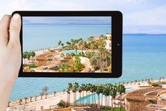 Tourist taking photo of waterfront on Dead Sea Royalty Free Stock Photos