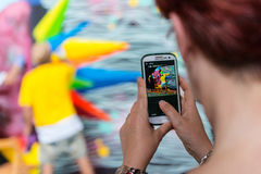 Tourist taking photograph of a colorful graffiti Royalty Free Stock Photography