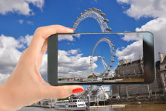 Tourist taking a photography with smartphone to London Eye on the banks of Thames River Royalty Free Stock Photography