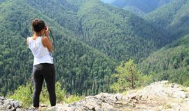 Tourist taking photos of forest hills in Slovak Paradise. Papuan young tourist woman - photographer girl taking photos hills with forest from viewpoint in Slovak stock photography