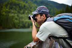 Tourist taking photos of a lake. Closeup of a tourist taking photos of a lake in the mountains Stock Images