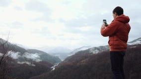 Tourist taking photos in montains stock video
