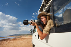Tourist taking photos from the open window of jeep Royalty Free Stock Photos