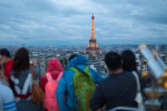 Tourist taking photos of Paris cityscape with Eiffel tower. Crowd of tourist taking photos of Paris cityscape with Eiffel tower at dusk from Arc de Triomphe Stock Photo