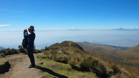 Tourist taking photos from the Rucu Pichincha  with the Antisana volcano in the background Royalty Free Stock Images