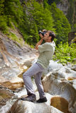Tourist taking photos of a waterfall. Caucasian tourist taking photos of a waterfall in the mountains Stock Photos