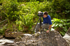 Tourist taking photos of a waterfall. Caucasian tourist taking photos of a waterfall in the mountains Stock Images