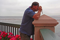 Tourist taking picture. Male tourist taking pictures at seaside over a railing Stock Images