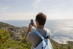 Tourist takin picture at island Cres, Croatia. Tourist taking picture of the Adriatic sea from the Lubenice highest point of the island Cres in Adriatic sea in Stock Photos