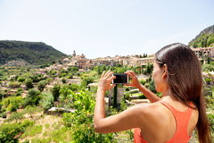 Tourist taking picture of Deia Village in Mallorca. Travel woman hiker using smartphone app to take a landscape photo of the Unesco World Heritage site on Stock Image