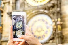 Tourist taking picture of a famous attraction with smartphone. Woman taking photo of the Prague astronomical clock in Czech Republic with mobile camera phone Stock Images