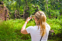 Tourist taking picture with her smart phone. In tropical forest Royalty Free Stock Photo