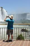Tourist taking picture of the Iguassu Falls. Tourist taking a picture on the Brazilian side of the Iguassu Falls in a sunny day of summer Stock Images