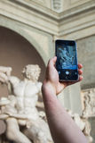 Tourist taking picture of Lacoon Statue. A tourist is taking a picture of the Sculpture of the Laocoön group during his trip to Rome, Italy Stock Photo