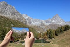 Tourist taking picture of Matterhorn or Breuil-Cervinia stock images