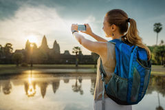 Tourist taking picture of the mysterious Angkor Wat, Cambodia. Young female tourist with backpack and smartphone taking picture of the ancient temple complex Stock Photography