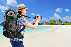 Tourist taking picture at a sandy beach Royalty Free Stock Photos